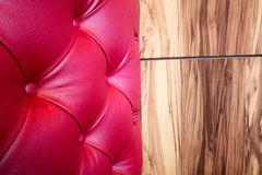 Red leather and wooden wall. Red sofa leather cushion against wooden wall, Textured background Royalty Free Stock Image