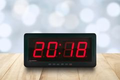 Red led light illuminated numbers 2018 on digital electric alarm clock face on wooden table top with blue Christmas lights bokeh. Red led light illuminated stock images