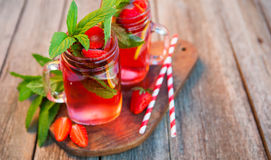 Red lemonade with strawberries and mint on an old wooden table i Royalty Free Stock Photos