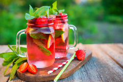 Red lemonade with strawberries and mint on an old wooden table i Stock Photography