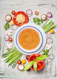 Red lentil in bowl and vegetables ingredients for healthy vegetarian cooking, top view Stock Photo