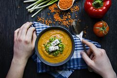 Red lentil cream soup decorated with fresh vegetables and herbs. A man eats soup. Veggie concept. Proper nutrition royalty free stock photos