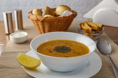 Red lentil soup. With lemon, mint and pepper on the table royalty free stock image