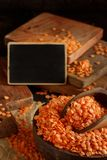 Red lentils in a bowl with a small chalkboard. Close up stock photo
