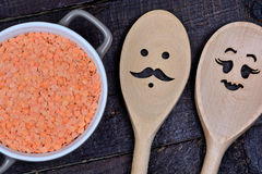 Red lentils in a ceramic pot with family wooden spoons Stock Image