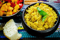 Red lentils with curry and dates and a salad of mango and tomato. On a dark wood background. tinting. selective focus on parsley Stock Image