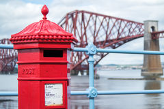 Red letterbox and Firth of Forth rail bridge Stock Image