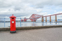 Red letterbox and Firth of Forth rail bridge Royalty Free Stock Image