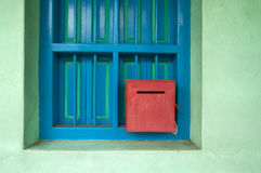 Red letterbox on green and blue wall. Retro style red letterbox against blue and green wall Royalty Free Stock Image