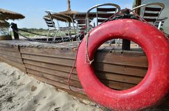 Red life belt on sea beach. Red life belt attached to elevated wooden floor of a sea beach restaurant stock photo