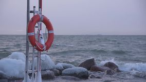 Red life buoy in the stormy winter weather by the Baltic Sea in Helsinki, Finland stock footage