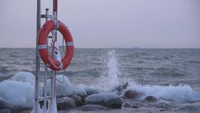 Red life buoy in the stormy winter weather by the Baltic Sea in Helsinki, Finland stock video