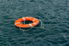 Red life buoy in the water Stock Photos