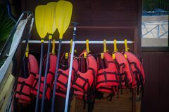 Red life jackets and yellow paddles at a beach hut are waiting f stock photos