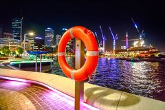 Red life preserver Perth. Red life preserver on foreground on walkway of Elizabeth Quay Marina in Perth Downtown, Western Australia. Esplanade and construction Stock Photography