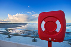 Red life ring by a beach at sunset. A red life ring in front of a long beach in Scotland at sunset. Photo taken by West Sands beach in St Andrews stock images