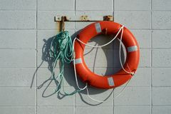 Red life saving ring hanging on a breeze block wall. Red life saving ring attached to a tangled green rope hanging on rusty hooks on a breeze block wall stock images