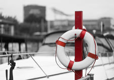 Red lifebelt in front of a marina Royalty Free Stock Photography
