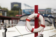 Red lifebelt in front of a marina Stock Images