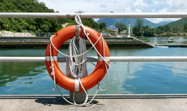 Red lifebelt, safety rope, pier near lake Stock Image