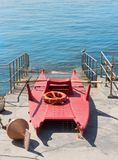 Lifeboat on a Waterfront. Red lifeboat on a waterfront Royalty Free Stock Photo