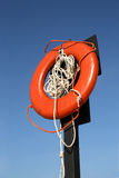 Red lifebuoy. Low angle view of red lifebuoy with rope on post, blue sky background Stock Photography