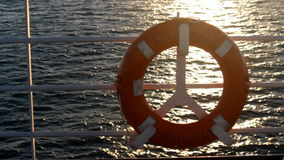 Red lifebuoy on a boat crossing the sea at sunset stock video footage
