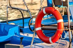 Red lifebuoy, fixed on deck of the yacht. Moored in the city marina Royalty Free Stock Photos