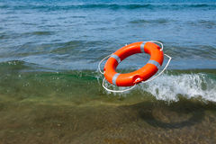Red lifebuoy flying in the sea wave. Red lifebuoy flying into the sea foamy waves on a sunny day at sea Stock Images