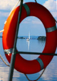 Red Lifebuoy. In front of the blue sea. Sailboat royalty free stock photography