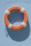 Red lifebuoy hanging on blue wall Stock Photos