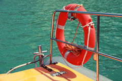 Red lifebuoy hanging on railings of rescue boat. Red lifebuoy hanging on railings of safety rescue boat Stock Image
