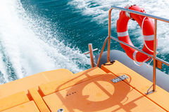 Red lifebuoy hanging on railings of rescue boat. Red lifebuoy hanging on steel railings of safety rescue boat Royalty Free Stock Image