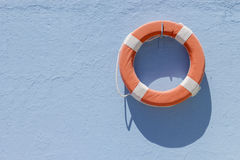 Red lifebuoy hanging on wall Stock Photography