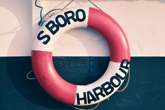 Red lifebuoy hanging on wall. With sigh of Scarborough Harbour Stock Images