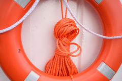 Red lifebuoy. Hanging on white wall Royalty Free Stock Images