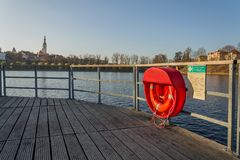 Red lifebuoy hanging on wooden pier, Jordan pond, Tabor, oldest dam in the Czech Republic, sunny autumn day, life insurance. Concept royalty free stock photography