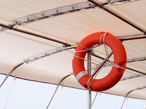 Red lifebuoy, life preserver hanging on roof of boat for fast safety rescue boat. Life Buoy on a Cruise Ship.  Stock Photo