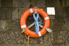 Red Lifebuoy. Red life ring mounted against a stone wall Royalty Free Stock Photo