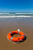 Red lifebuoy lying on the sand on the beach. Red lifebuoy with a rope lying on the sand against the background of the southern sea on a sunny day Royalty Free Stock Image