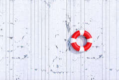 Red lifebuoy on a old grunge wooden plank wall, summer concept Stock Image