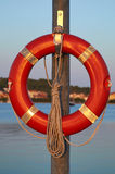 Red lifebuoy. On a pole on the quay Royalty Free Stock Images