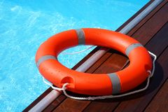Red lifebuoy pool ring float. On blue water. Life ring floating on top of sunny blue water. Life ring in swimming pool Royalty Free Stock Photography