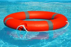 Red lifebuoy pool ring float. On blue water. Life ring floating on top of sunny blue water. Life ring in swimming pool Stock Images