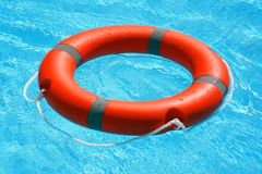Red lifebuoy pool ring float. On blue water. Life ring floating on top of sunny blue water. Life ring in swimming pool Royalty Free Stock Photo