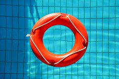 Red lifebuoy pool ring float, ring floating in refreshing. Red lifebuoy pool ring float, ring floating in refreshing blue swimming pool. Red float floating in Royalty Free Stock Photos
