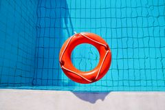Red lifebuoy pool ring float, ring floating in refreshing. Royalty Free Stock Images