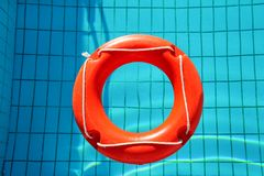 Red lifebuoy pool ring float, ring floating in refreshing. Red lifebuoy pool ring float, ring floating in refreshing blue swimming pool. Red float floating in Royalty Free Stock Images