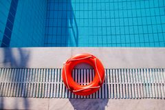 Red lifebuoy pool ring at swimming pool. Red pool ring in cool b. Lue refreshing blue pool, room for your. Red pool ring and pool summer background. Summer Stock Images