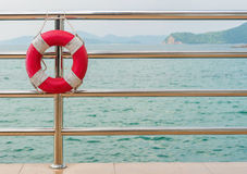 red Lifebuoy on railing by the sea Royalty Free Stock Images